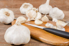 White garlic bulbs and cloves. On wooden cutting board Royalty Free Stock Photo