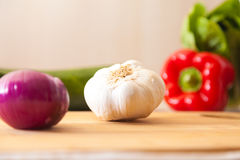 White garlic lies on a board with other vegetables Stock Photo