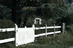 White gate. Bright white wooden gate leading through a mysterious thick garden to an old granite Breton house; image partly desaturated for mysterious and Royalty Free Stock Images