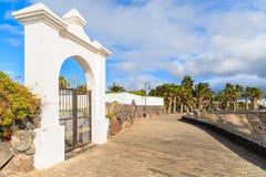 White gate to luxury hotel on coastal promenade Royalty Free Stock Image