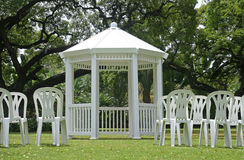 White gazebo with chairs outdoors. White gazebo and chairs outdoors with green grass surrounded by trees Stock Photography