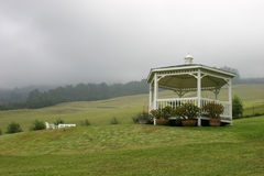 White gazebo on hillside. White gazebo on a hillside with a mist-covered mountain in the background royalty free stock photo