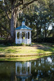 White Gazebo by Lake Under Spanish Moss Royalty Free Stock Image