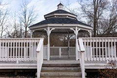 White gazebo with steps and fence stock image