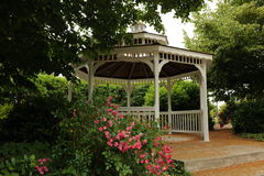 White Gazebo. Surrounded by trees bushes and  pink flowers with brick floor and steps Royalty Free Stock Photo
