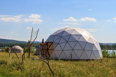 White geodesic dome on a sunny summer day in field royalty free stock photography