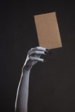 White ghost or witch hand with black nails holding blank cardboa. Rd, Halloween theme stock photos