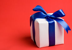 White gift with a blue ribbon royalty free stock photography
