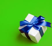 White gift in a blue  ribbon on a green Stock Image