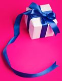 White gift in a blue  ribbon on a pink Royalty Free Stock Images