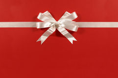 White gift bow ribbon red paper background straight horizontal Stock Photography
