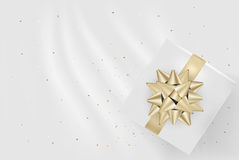 White Gift Box And Gold Bow Ribbons With Confetti On Light Silk Stock Photo