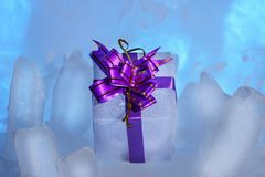 white gift box with a beautiful purple bow lies on the blue ice. Royalty Free Stock Photography