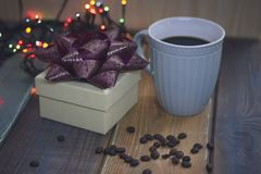 White gift box, blue cup, coffee beans on the tablen Stock Image