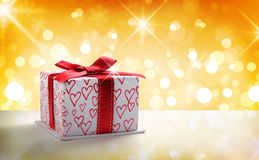 White gift box with bow and hearts Golden bokeh front Royalty Free Stock Photography