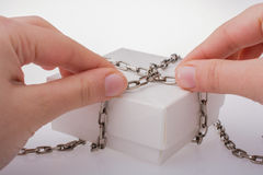 White gift box with chain in hand Royalty Free Stock Image