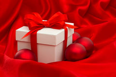 White gift box with christmas balls decoration over red silk Royalty Free Stock Images