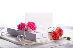 White gift box with flowers. White gift box with carnation flowers with high key white background Royalty Free Stock Photography