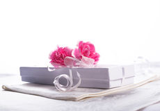 White gift box with flowers. White gift box with carnation flowers with high key white background Stock Photo