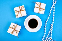 White gift box with gold ribbon. Near cup of coffee on blue background. Flat lay. Copy space Royalty Free Stock Images