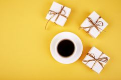 White gift box with gold ribbon. Near cup of coffee on yellow background. Flat lay. Copy space Royalty Free Stock Image