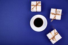 White gift box with gold ribbon. Near cup of coffee on blue background. Flat lay. Copy space Stock Photos