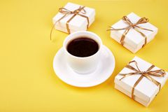 White gift box with gold ribbon. Near cup of coffee on yellow background. Flat lay. Copy space Royalty Free Stock Photos