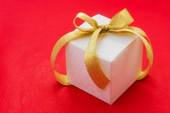 White gift box with a golden ribbon and bow Royalty Free Stock Photography