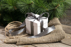 White gift box with grey ribbons, cristmas tree branch and rope Royalty Free Stock Photos
