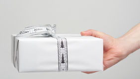 White gift box in hand. Giving with ribbon isolated on white Stock Photography