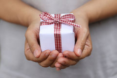 White Gift box on hand and Red Ribbon on gift box,Concept christ Stock Images