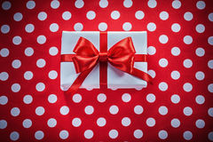 White gift box with knot on polka-dot red fabric holidays concep Stock Photo