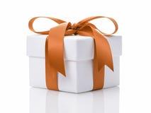 White gift box with orange ribbon bow Royalty Free Stock Photos