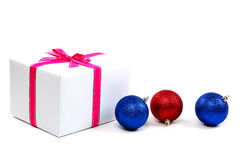 White gift box with pink ribbon and christmas balls. Stock Photography