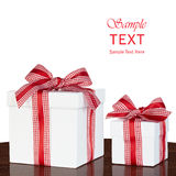 White Gift Box Present Red & White Gingham Checked Ribbon. White Gift Box Present With Red & White Gingham Checked Ribbon Bow On Vintage Dark Wood Table Isolated Stock Image