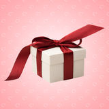 White gift box with red bow. A white box tied with a red ribbon bow on pink abstract background with hearts. The best gift for Christmas, Birthday, Valentines's Royalty Free Stock Images