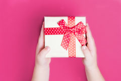 White gift box with red bow in the children`s hands on pink backgroundclose up stock images