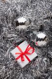 White gift box with a red bow on silver garland. Decorative white gift box with a red bow on silver Christmas garland with Christmas balls Royalty Free Stock Image