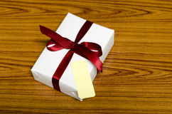White gift box and red ribbin with tag Royalty Free Stock Photo