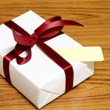 White gift box and red ribbin with tag Royalty Free Stock Photos