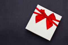 White gift box with red ribbon on black background. stock photo