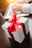 White Gift Box with Red Ribbon and Bow Near Man Typing on Laptop Stock Image