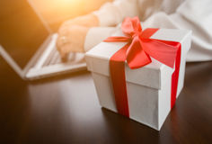 White Gift Box with Red Ribbon and Bow Near Man Typing on Laptop Royalty Free Stock Photo