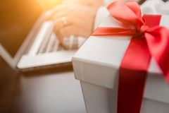 White Gift Box with Red Ribbon and Bow Near Man Typing on Laptop Royalty Free Stock Photography