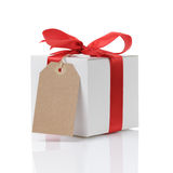 White gift box with red ribbon bow and paper tag Stock Photography