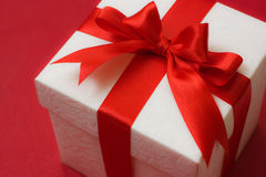 White gift box with a red ribbon and bow on red ba Royalty Free Stock Photo