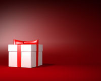 White Gift Box with Red Ribbon and Bow on the Red Background Royalty Free Stock Images