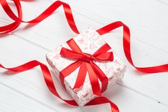 White gift box with red ribbon bow. On wooden background Royalty Free Stock Photo