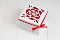 White gift box with red ribbon bow. Boxing day. White gift box with red ribbon bow on wooden background Stock Images