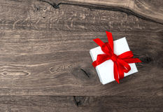 White gift box with red ribbon bow on wooden background Stock Photo